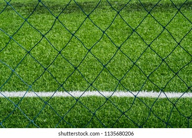 close up of football field behind chain link fence.