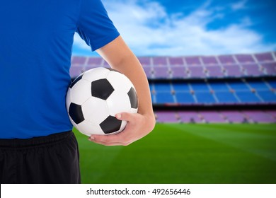 close up of football player holding soccer ball on field of stadium