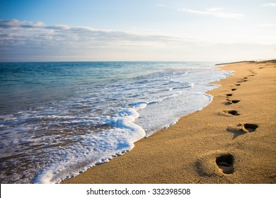 close up of footprints in the sand on the beach at sunset