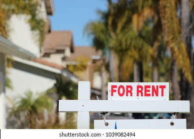 "Close up of a ""For Rent"" sign in a typical Southern California neighborhood"