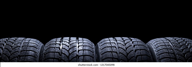 Close up of four car tires wheels isolated on black background copy space for text, studio shot no people