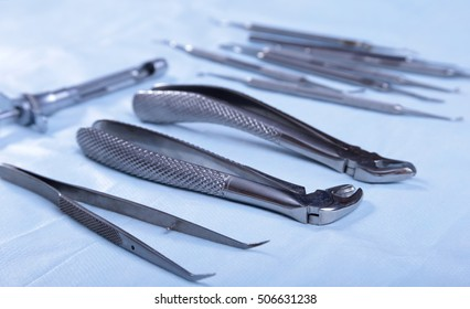 Close up of four different stainless steel surgical forceps and scalpel isolated on white background.