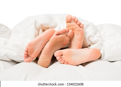 Close up of four feet in a white bed
