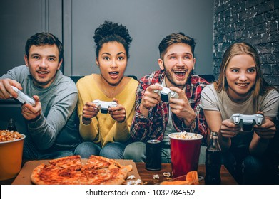 Close up of four friends sitting together and playing the game. All of them want to win. They are playing very intensive. Also they are enjoying the time spending together.