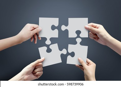 Close up of four hands holding jigsaw, Concept for teamwork Building a success.