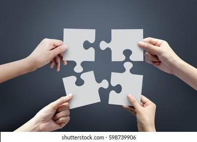 Nahaufnahme von vier Händen halten jigsaw, Konzept für Teamwork Building a success.