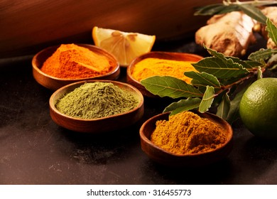 Close up Four Plates with Assorted Powdered Food Spices on a Wooden Table with Fresh Lemon.