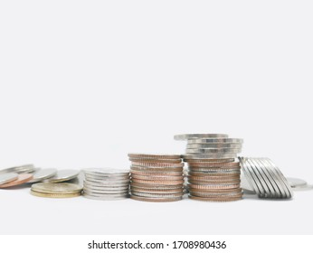 Close up of four stacks of coins on a white background and many coins on the back. Income, profits, finance, Investment, Interest and Saving money concept.