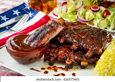 Close up of Fourth of July picnic with barbeque ribs sitting on white plate with corn on the cob, salad and glass of iced tea