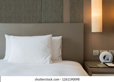 Close up fragment of bedroom with reading lamp and digital alarm clock in modern home or hotel.
