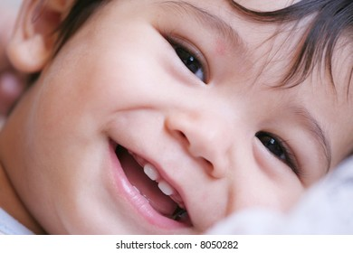 Close up framing on face of beautiful baby boy smiling