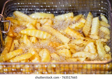 close up French Fries Potatoes cooking in basket of Frying Machine , deep fried  in Hot Boiling Oil