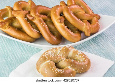 Close up of fresh baked soft salted pretzels on a wooden background.