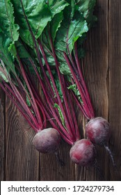 Close up of fresh beetroot with leaves on rustic wooden background, top view