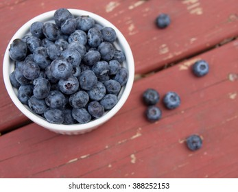Close up fresh blueberries on red wooden background, top view, horizontal