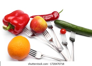 close up of fresh cherry tomato, red peppers, cucumber, apple and orange fruits on forks on white background. Healthy eating and vegetarian food, cooking concept.