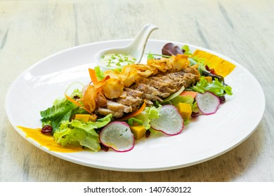 close up of fresh chiken salad italian style with topinambur, artichokes crunchy  chips, mixed greens, radish sliced ,lemon mayonnaise herbs sauce, slow cooked chicken in a white plate, natural light