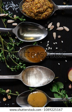 Close up of fresh herbs, sunflower and sesame seeds, salt with condiments and ingredients in spoons arranged in a line on black background, top view