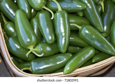 Close up of fresh, hot jalapeno peppers heaped in a basket