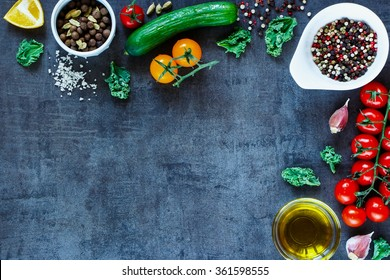Close up of fresh ingredients for salad with cucumber and tomatoes on dark vintage background. Top view, copy space. Cooking, Healthy Eating or Vegetarian concept.