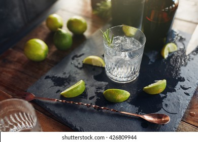 Close up of fresh made cocktail drink with lemon slices and spoon on the board.