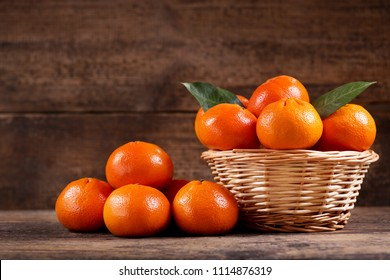 close up of fresh mandarin oranges fruit  in a wooden basket