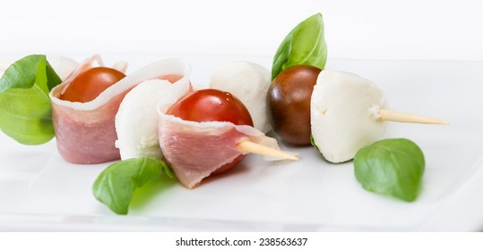 close up of a fresh mozzarella and tomato appetizer with basil and proscuitto on a white plate
