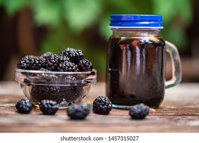 Close up fresh mulberries fruit in bowl and juice in jar