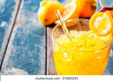 Close Up of Fresh Orange Frozen Granita Slush Drink Garnished with Orange Wedge and Served in Glass with Striped Straw on Weathered Blue Wooden Picnic Table with Oranges in Background - Copy Space