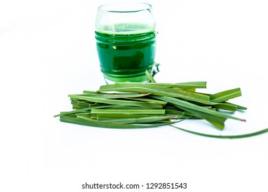 Close up of fresh organic extracted juice of lemon grass isolated on white in a transparent glass with raw Indian lemon grass or lili chai or Cymbopogon.