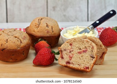 Close up of fresh, organic Strawberry muffins with fresh strawberries and whipped butter.  Selective focus on sliced muffin.