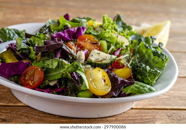 Close up of fresh organic super food salad in white bowl sitting on wooden table