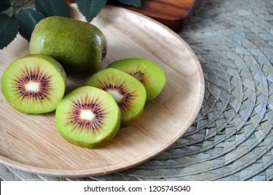 Close up fresh pieces of red kiwifruit on wooden plate