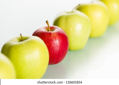 "Close up of fresh red apple standing out from row of green apples, concept ""Dare to be different.""."