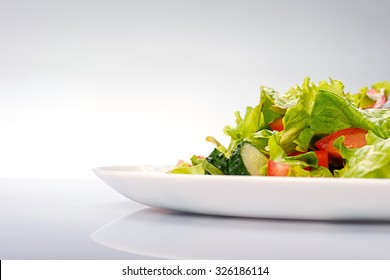 Close up of fresh salad of lettuce, cucumber and tomato on plate for healthy eating. Isolated on blue background