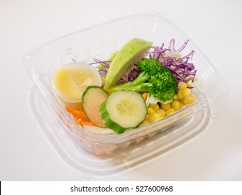 The close up of fresh salad set in the clear plastic box.