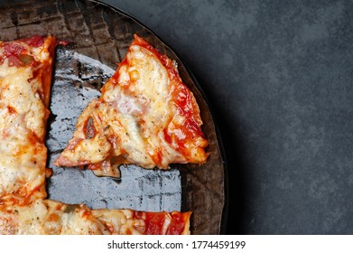 Close up of a fresh Slice of a Pizza in an rustic iron Pan on a Slate Plate