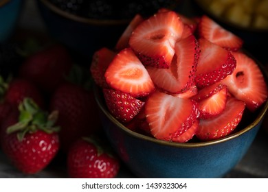 Close up of fresh sliced strawberries in blue bowl low key.