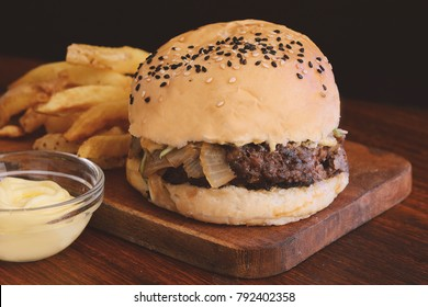Close up of fresh tasty burger and french fries on wooden cutting board. Unhealthy food concept.