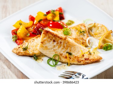 Close up of fresh tilapia fish fillet with bbq grilled vegetables on white dish or plate on wooden background