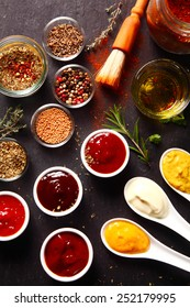 Close up Fresh Various Spices and Sauces on the Black slate kitchen Table