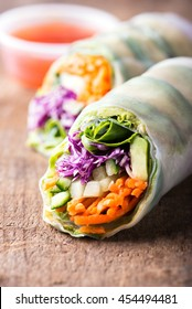 close up of fresh vegan rice paper spring rolls with raw vegetables (cucumber, avocado, lettuce, carrots, red cabbage) inside, sweet chili dipping sauce behind, isolated over dark, wooden background