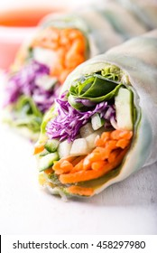 close up of fresh vegan rice paper spring rolls with raw vegetables (cucumber, avocado, lettuce, carrots, red cabbage) inside, sweet chili dipping sauce behind, isolated over white, wood background