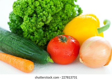 Close up of fresh vegetables. Tomato, cucumber, pepper, carrot, parsley, onion.