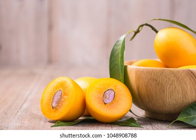 Close up fresh yellow marian plum fruit (Mayongchid in Thai name) on wooden table