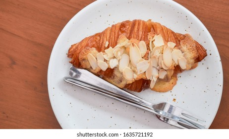 Close up freshly baked croissants on white plate, top view