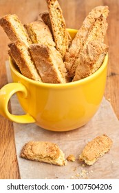 Close up of freshly baked, homemade and warm almond biscotti in a large, ceramic, yellow cup on parchment paper square on a wood serving board