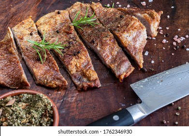 Close up of freshly cooked pork Secreto de ventresca pure iberico, iberian pig cut, with himalayan pink salt, pepper in grains, rosemary and a knife on a wooden board