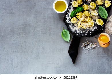 Close up of freshly made raw Italian pasta tortellini, olive oil, flour and basil leaves on light grey vintage background with space for text, top view.