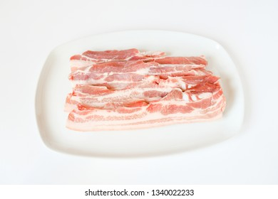 Close up freshness cutting slide pork belly raw or streaky pork on  white background. .A meat boneless cut of fatty meat from the belly of a pig. This dish is considered a delicacy in many countries.